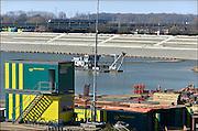 Nederland, Nijmegen, 12-3-2015 Aan de overkant van de Waal bij Lent wordt druk gewerkt aan het creeren van een nevengeul in de rivier om bij hoogwater een betere waterafvoer te hebben. De zandzuiger in het water bij de nieuwe recreatiekade. Op de voorgrond werkzaamheden aan de vernieuwde n325.Het is een omvangrijk project waarbij onder meer de pijlers van het spoorviaduct een bredere basis moeten krijgen omdat die straks in de loop van het water staan. Ook de n325 die vanaf de Waalbrug naar Arnhem loopt moet over 400 meter opnieuw worden aangelegd omdat het talud vervangen wordt door pijlers. De weg wordt via een bypass omgeleid. Het dorp veurlent komt op een kunstmatig eiland te liggen met twee bruggen als ontsluiting. Een voetgangersbrug en de andere voor normaal verkeer. Inmiddels begint de nieuwe kade aan de noordkant van deze geul vorm te krijgen. Ruimte voor de rivier, water, waal. In de nieuwe dijk wordt een drempel gebouwd die stapsgewijs water doorlaat en bij hoogwater overloopt. Measures taken by Nijmegen to give the river Waal, Rhine, more space to flow during highwater and to prevent the risk of flooding. Room for the river. Reducing the level, waterlevel. Foto: Flip Franssen/Hollandse Hoogte
