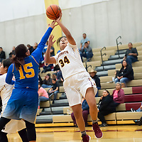 Kylie Tsikewa (15) of Zuni gets her hand in the face of Emerald Toddy (34) of Rehoboth to contest the shot during the championship game in Rehoboth on Saturday. Zuni won 48-37.