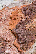 Orange rock patterns in Death Valley National Park, California, USA. More than 5 million years ago, multiple volcanic eruptions deposited ash and minerals which chemically altered into a colorful paint pot of elements (iron, aluminum, magnesium and titanium).