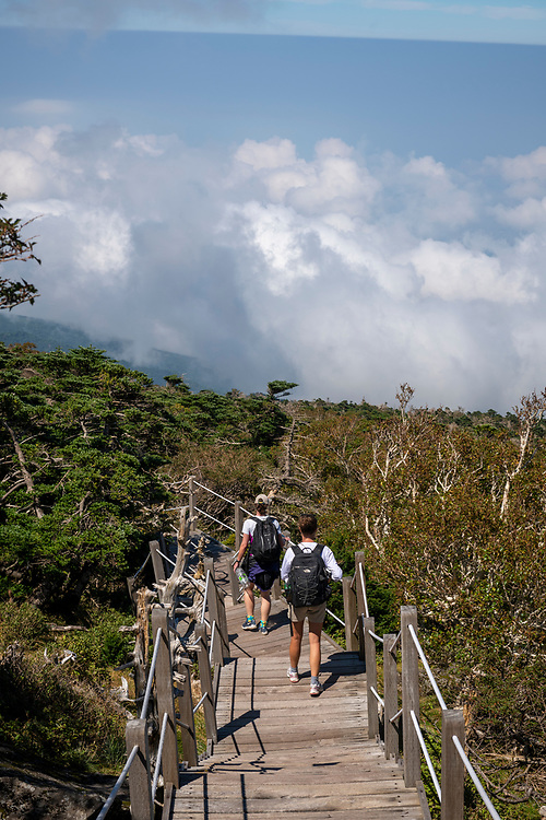Hallasan National Park, South Korea - September 16, 2019: Two women visiting South Korea from Poland and the U.K. begin the descent down the Gwaneumsa Trail from the summit of Hallasan, South Korea's highest mountain located in Hallasan National Park, Jeju Island.