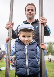 """13 August 2016, Norrbyskär, Umeå, Sweden: Issam, a refugee child from Syria practices walking on stilts, helped on by his father, during the Kul-Tur Fest (""""Culture Festival""""). The event, which attracted hundreds of people, set out to offer a meeting place for Swedish culture and new forms of cultural expression, and featured baking competitions, dance workshops, book discussions, fingernail painting and music, among other things. Parental consent obtained."""