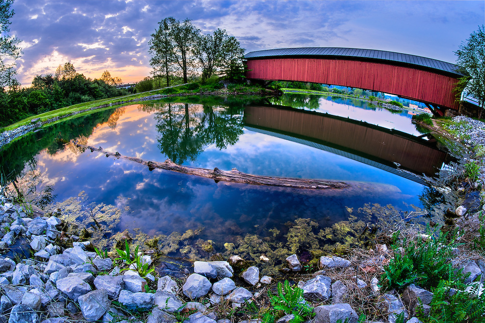 The covered bridge and pond at Pumpkin Park in Milton, West Virginia at sunset.