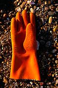 Single orange rubber glove washed up on beach, on North Sea coast, Shingle Street, Suffolk, England, UK