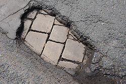 Pot hole in the tarmac exposing the cobbled paving