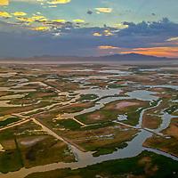 A sunset glows over the marshy shoreline of Great Salt Lake near Salt Lake City, Utah.  Behind is Antelope Island.