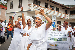 Yara Pollack, left, Marcella, and Marie Paul portray the striking coal workers.  10th Annual Dollar Fo' Dollar Culture & History Tour commemorating the anniversary of the successful protest  demanding better pay by Queen Coziah and the 19th century coal laborers in the streets of downtown Charlotte Amalie.  12 September 2015.  St. Thomas, VI.  © Aisha-Zakiya Boyd