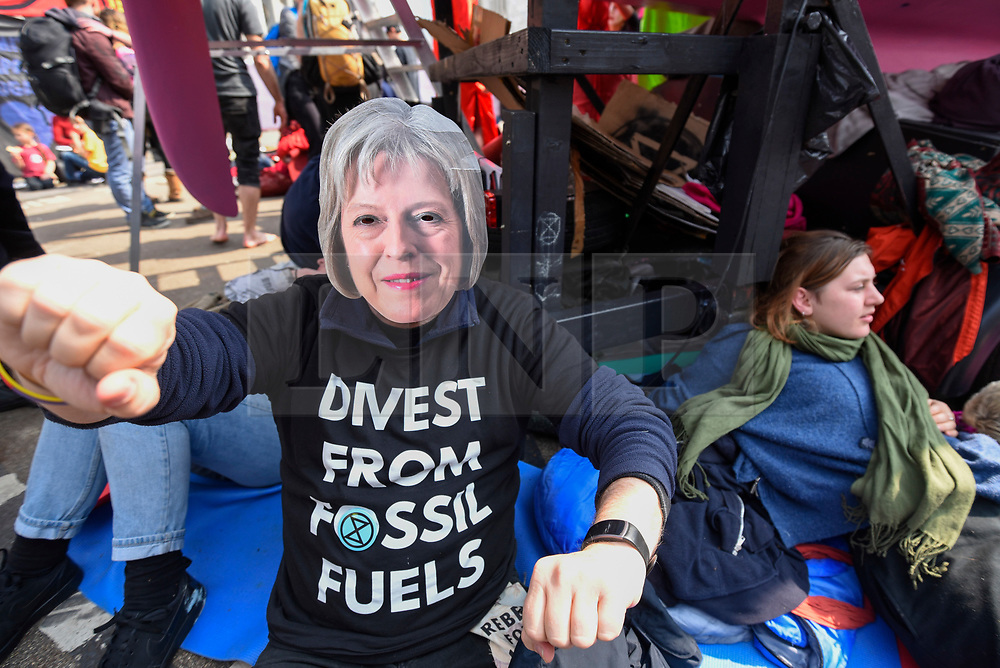 """© Licensed to London News Pictures. 17/04/2019. LONDON, UK.  A protester wears a Theresa May face mask at Oxford Circus during """"London: International Rebellion"""", on day three of a protest organised by Extinction Rebellion, demanding that governments take action against climate change.  Marble Arch, Oxford Circus, Piccadilly Circus, Waterloo Bridge and Parliament Square have been blocked by activists in the last three days.  Police have issued a section 14 order requiring protesters to convene at Marble Arch only so that the protest can continue.  Photo credit: Stephen Chung/LNP"""
