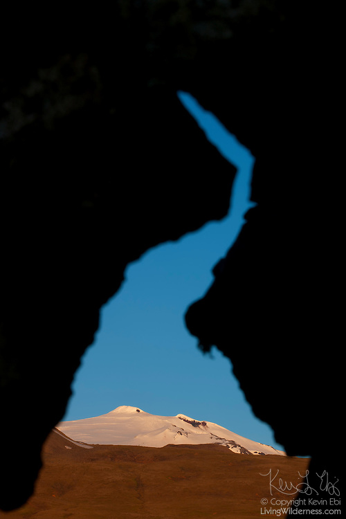 """Snæfellsjökull, a 1,446 meter (4,744 foot) stratovolcano, is framed by a natural arch in a lava field in western Iceland. The volcano, which is active, last erupted approximately 1,800 years ago, creating lava fields at its base. The mountain is technically named Snæfell; Snæfellsjökull is the name of the glacier at its peak. It is commonly called Snæfellsjökull, however, to avoid confusing it with several other mountains with the same name. Snæfellsjökull means """"snow glacier mountain,"""" and it was featured in the 1864 novel """"A Journey to the Center of the Earth"""" by Jules Verne.."""
