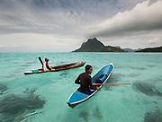 Kids fishing coral fish on dug out canoes, near Bodgaya island.