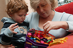 Portrait of a woman and little boy selecting chocolates,