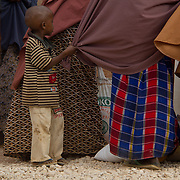 A small boy tugs on his mother's burka as she waits for relief distribution. Wajir, North Eastern Kenya.