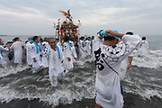 Mikoshi are taken into the surf during the Hamaorisai matsuri in Chigasaki, Kanagawa, Japan. Monday July 17th 2017.  This festival is celebrated on Marine Day in Japan. Over 40 mikoshi (portable shrines) are paraded through the night to arrive on the coast at Southern Beach where they are blessed in a Shinto ritual before being carried into the waves to be purified.