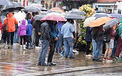 Tourists under umbrellas near Windsor Castle as a yellow weather warning for rain has been issued for parts of the UK.