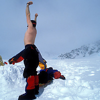 USA, Alaska, Denali National Park, (MR) Rick Ford stretches in morning sun at camp during Mount McKinley climb