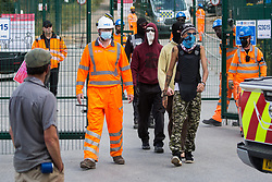Harefield, UK. 22 July, 2020. Activists from HS2 Rebellion who had occupied machinery and trees in order to hinder tree felling for the HS2 high-speed rail link are escorted to a works site gate by HS2 workers and security guards. Environmental activists continue to protest against HS2, which is currently projected to cost £106bn and will remain a net contributor to CO2 emissions during its projected 120-year lifespan, from a series of wildlife protection camps along its route.