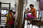 Weavers at Amity Carpent Factory. Amity Factory does not employ children and is a licensee of the GoodWeave Foundation and their carpets carry the GWF label.The weavers work according to the design,printed on paper hanging above them. Most are women and many mothers and they work inthe factory 12-14 hours /day 6 days/week. The Good Weave Foundation is a charity set up in partnership with the Nepalese carpet industry. The aim is to eliminate child labor in all carpet factories in Nepal. Factories which do not employ children can sign up with the charity and become a licensee to the GWF brand and label their carpets with the GWF label which promises any buyers abroad that no children were involved in making the carpets.
