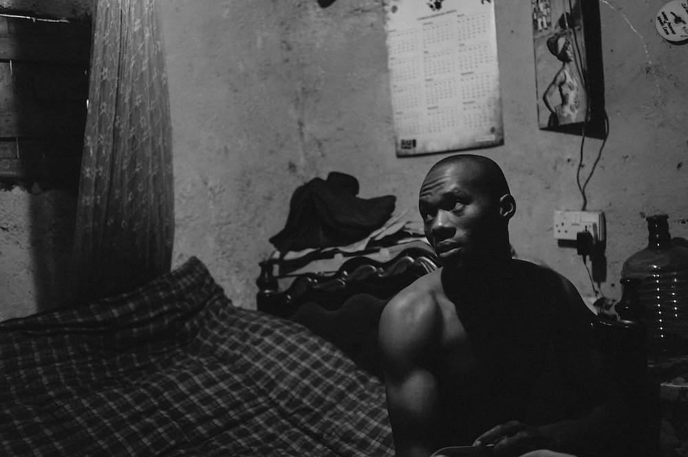 """NAIROBI, KENYA - AUGUST 16, 2011: Kamau """"Kelly"""" Ng'ang'a changes clothes in his one room apartment after excercising. Unable to find regular work in the slum, Ng'ang'a moved into this room in January of 2011 after a friend volunteered the space to him free of rent.<br /> <br /> Within Kenya's progressive youth culture is the Kibera Olympic Boxing Club, a group of low-income adolescents from the slum whose leader uses boxing as a way to engage with idle youth. The group's ethnic diversity is remarkable given Kenya's 2008 post-election violence in which people from several tribes were forced violently out of slums. Together, these boxers represent a nascent trend of cross-tribe brotherhood in a healing nation."""