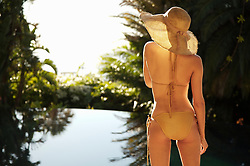 Back of young woman standing by exotic swimming pool