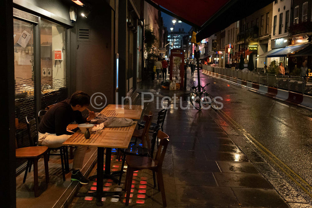 On a rainy night in Soho, a man eats noodles overlooking a pedestrianised Dean Street during the coronavirus pandemic, on 27th August 2020, in London, England.