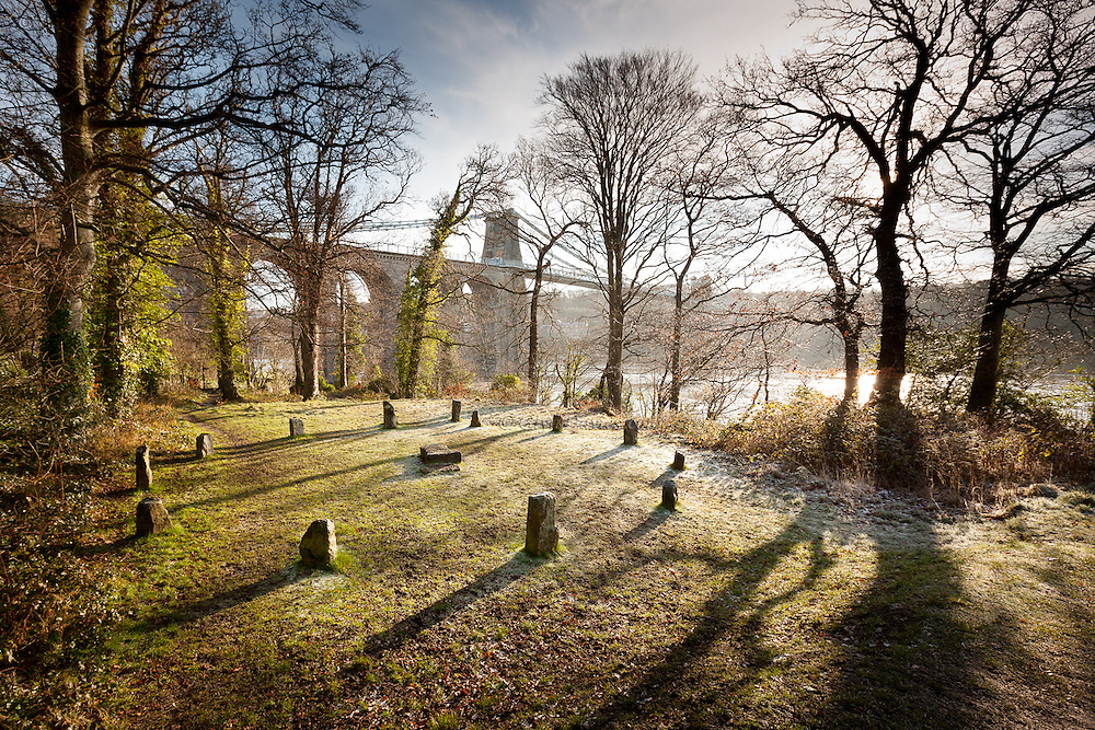 Early morning frost on the banks of the Menai Strait, Anglesey, with the beautiful Menai Suspension Bridge looming in the background, built and completed by Sir Thomas Telford in 1826. The stone circle is monumental rather than real.