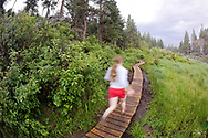 A young woman runs along the Deschutes River Trail near downtown Bend, Oregon.  The Deschutes River Trail is one of the premier running trails around Bend.  It twists and turns along the lava-strewn Deschutes river. (Model Released)