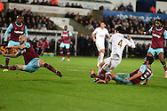 a shot at goal from Ki Sung-Yueng of Swansea city (4) appears to hit the arm and gets blocked by James Collins of West Ham (far left) but referee Lee Mason does not give a penalty.Barclays Premier league match, Swansea city v West Ham Utd at the Liberty Stadium in Swansea, South Wales  on Sunday 20th December 2015.<br /> pic by  Andrew Orchard, Andrew Orchard sports photography.