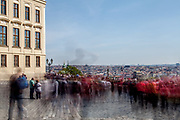 "Crowds walking across ""Hradcany Square"" (Hradcanske Namesti) towards the panoramic view at the Prague cityscape. On the left Prague Castle."