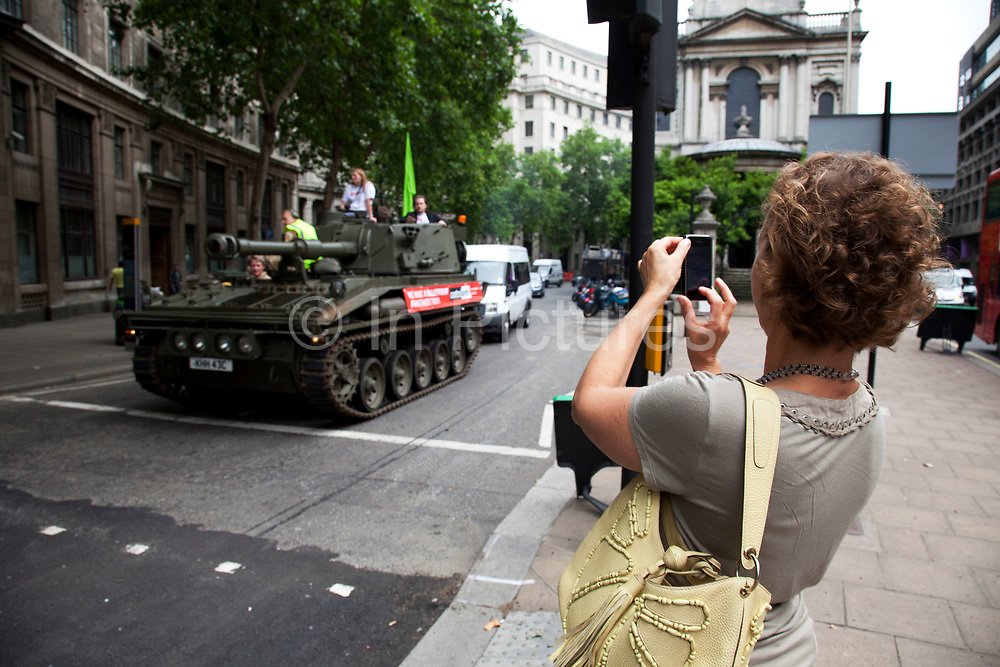 Woman photographs the tank with her mobile phone as it passes along Aldwych. Campaigners and supporters from Oxfam and Amnesty International, as part of the Control Arms coalition, drive an Abbot gun tank around central London to highlight the need for a global Arms Trade Treaty (ATT) to be agreed during a United Nations conference next month (July 2012). London, England, UK. 27th June 2012.