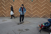 A young man on a skateboard passes the zigzag battens of a construction hoarding at Notting Hill, on 13th March 2018, in London, England.