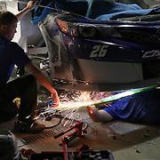 Crew members work on the car of Cole Whitt during the  56th Annual NASCAR Daytona 500 practice session at Daytona International Speedway on Wednesday, February 19, 2014 in Daytona Beach, Florida.  (AP Photo/Alex Menendez)
