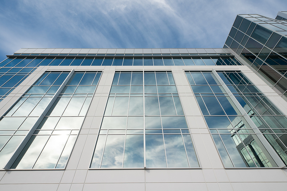 Commercial office tower and real estate building exterior, looking up towards sky