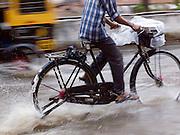 A cyclist rides through flooded street during the monsoon season, Cochin, Kerala, India