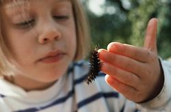 Young girl watching hairy caterpillar crawl across her fingers,