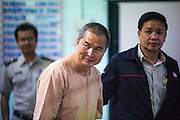 """23 JANUARY 2013 - BANGKOK, THAILAND:   SOMYOT PRUESAKASEMUK walks through the holding area of Bangkok Criminal Court on his way to sentencing Wednesday. Somyot was sentenced to 11 years imprisonment Wednesday for violations of Thailand's """"Lese Majeste"""" laws. He was arrested on April 30, 2011, and charged under article 112 of Thailand's penal code, which states that """"whoever defames, insults or threatens the King, the Queen, the Heir-apparent or the Regent, shall be punished with imprisonment of three to fifteen years"""" after the magazine he edited, """"Red Power"""" (later changed to """"The Voice of Thaksin"""") published two articles by Jit Pollachan, the pseudonym of Jakrapob Penkair, the exiled former spokesman of exiled fugitive former Prime Minister Thaksin Shinawatra. Jakrapob, now living in Cambodia, has never been charged with any crime for what he wrote.     PHOTO BY JACK KURTZ"""