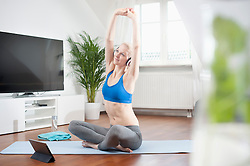 Young woman stretching her body and listening to music in living room, Bavaria, Germany
