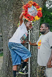 29 August 2014. Lower 9th Ward, New Orleans, Louisiana. <br /> Survivors of the storm. Robert Green, rescued from floodwaters, hangs a memorial wreath for his mother and grand daughter, both victims of hurricane Katrina. Green has made the wreath hanging an annual event on Tennessee Street in the Lower 9th Ward.  <br /> Photo; Charlie Varley/varleypix.com