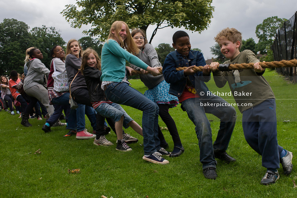 Local children heave-ho on a large rope for the best of three tug o war games during a community park festival.