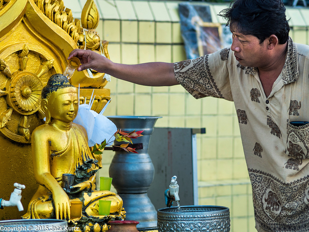 27 OCTOBER 2015 - YANGON, MYANMAR: People pray and make merit at Botataung Paya (Pagoda). Botataung Paya is located in downtown Yangon, Myanmar, near the Yangon river. The pagoda was first built by the Mon around the same time as was Shwedagon Pagoda—according to local belief, over 2500 years ago. The paya is hollow within, and houses what is believed to be a sacred hair of Gautama Buddha.    PHOTO BY JACK KURTZ