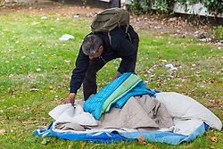 A man packs up his bedding on the litter-strewn central island of Park Lane, Mayfair, near Marble Arch. Over the last few years London has seen increasing numbers of Eastern European beggars and street performers on its streets as they flock to the UK and other wealthier countries to take advantage of people's generosity. London, August 02 2019.