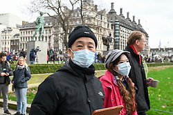 © Licensed to London News Pictures. 31/01/2020. LONDON, UK.  Tourists from China wear facemasks as they walk through Parliament Square.  It has been reported that Chief Medical Officer Professor Chris Whitty has confirmed that two people in England have tested positive for the coronavirus.  Photo credit: Stephen Chung/LNP