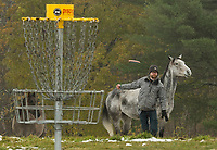 Frank Wruk makes his putt shadowed by one of the Castle in the Clouds horses during Sunday's Disc Golf Tournament.  (Karen Bobotas/for the Laconia Daily Sun)