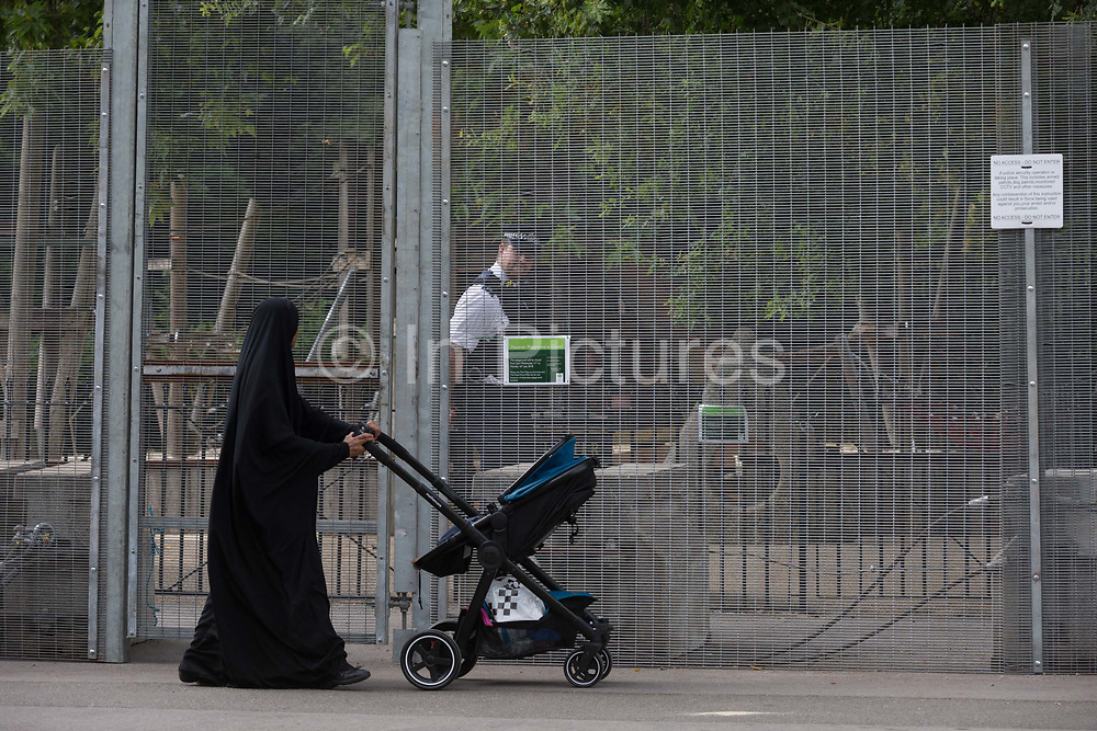A Muslim lady walks past UK Met police officers who guard a temporary perimeter fence encircling Winfield House, the official residence of the US Ambassador during the visit to the UK of US President, Donald Trump, on 12th July 2018, in Regents Park, London, England.