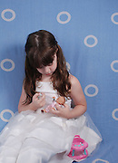 Girl of 5 in white dress feeds her doll with a syringe