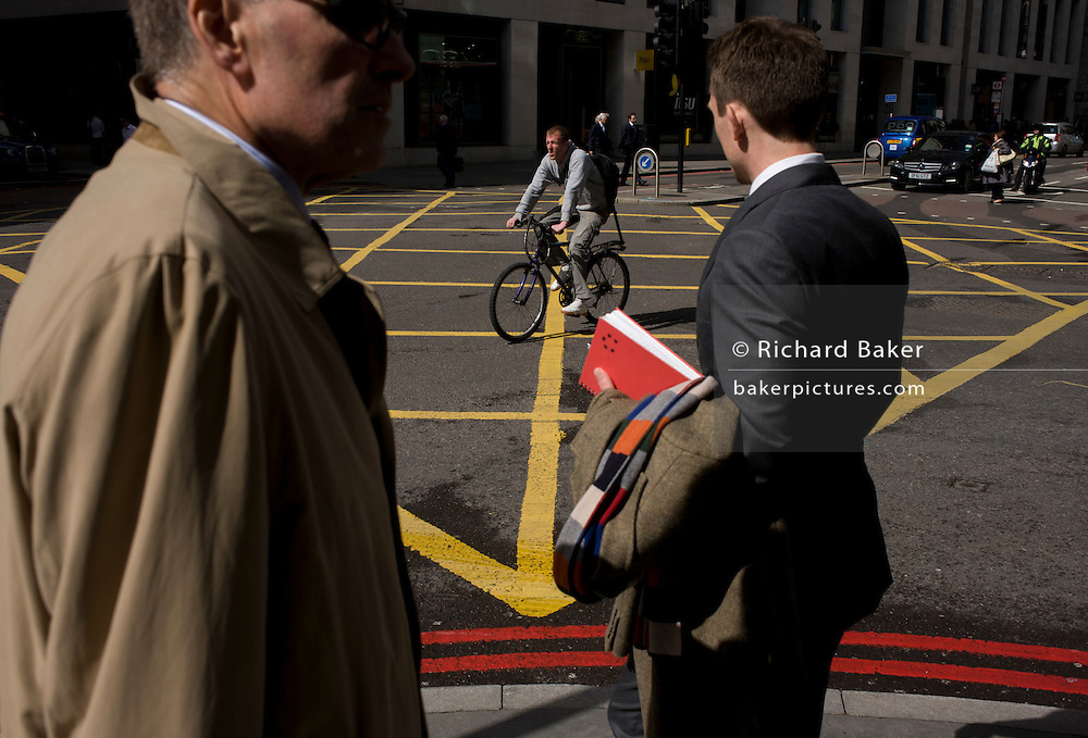 Pedestrians and cyclist who rides over a yellow box junction grid in a City of London street.