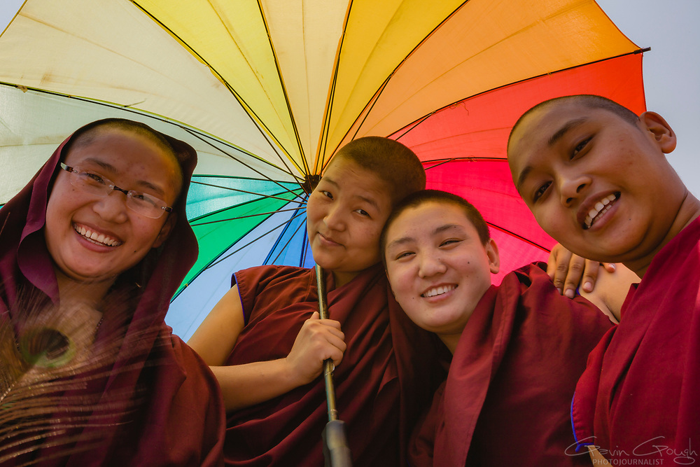 Tibetan Buddhist monks holding a colourful rainbow umbrella for protection from the sun during a pilgrimage to one of the largest Buddhist stupas in the world, Boudhanath Stupa, Boudhanath (Boudha), Nepal