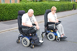 Disabled couple crossing the road in motorised wheelchairs,