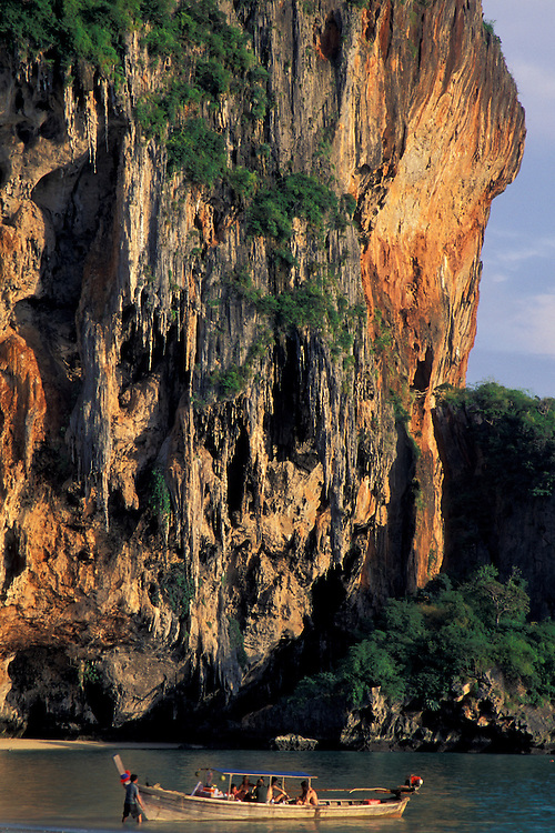 Asia, Thailand, Southern Thailand, near Krabi, Hat Tham Phra Nang Beach, Long-tailed boat used to ferry tourists to beaches waits below a karst cliff
