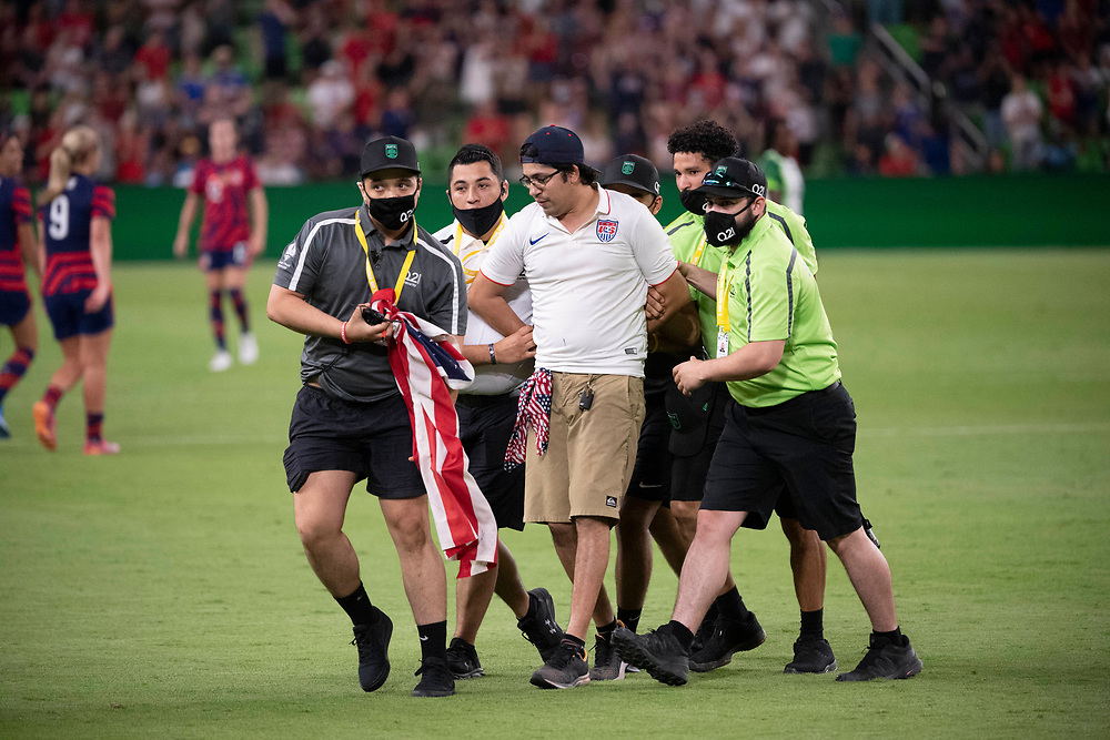 Security detains a man who tried to run onto the playing field at the end of the match of the US Women's National Team (USWNT) 2-0 victory over Nigeria, in the first match at Austin's Q2 Stadium. The U.S. women's team, an Olympic favorite, is wrapping up a series of summer matches to prep for the Tokyo Games. Press scored a goal in the win for USA Soccer.