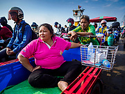 22 JANUARY 2019 - PHRA PRADAENG, SAMUT PRAKAN, THAILAND:  Passengers on a tuk-tuk on a motorcycle and vehicle ferry crossing the Chao Phraya River in Phra Pradaeng. The use of vehicle ferries across the river has gone down as the government has built bridges to connect communities on both sides of the river. The Phra Pradaeng ferries are the busiest vehicle ferries in the Bangkok metropolitan area. Since the BTS Skytrain now comes close to the ferry, the number of commuters going into Bangkok that use the ferry has increased.     PHOTO BY JACK KURTZ