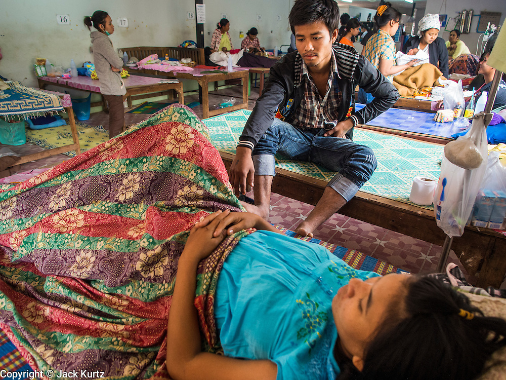 05 MARCH 2014 - MAE SOT, TAK, THAILAND: A man sits with his wife in the OB/Gyn ward at the Mae Tao Clinic. The Mae Tao Clinic provides  healthcare to over 150,000 displaced Burmese per year and is the leading healthcare provider for Burmese along the Thai-Myanmar border. Reforms in Myanmar have alllowed NGOs to operate in Myanmar, as a result many NGOs are shifting resources to operations to Myanmar, leaving Burmese migrants and refugees in Thailand vulnerable.     PHOTO BY JACK KURTZ